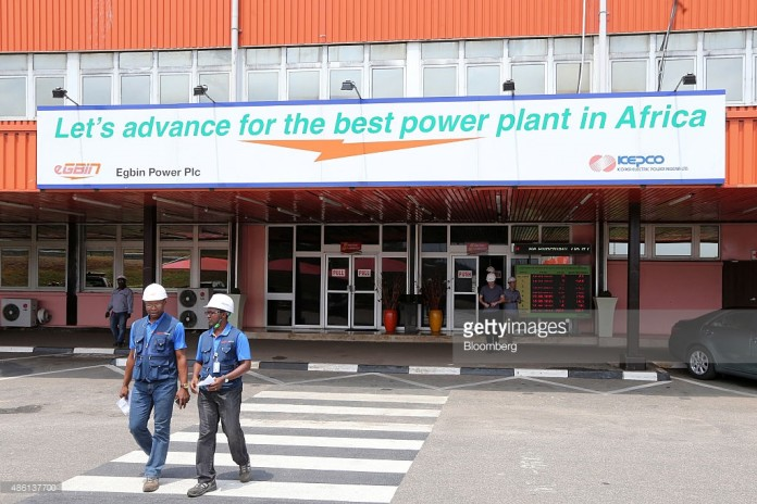Employees exit the newly renovated energy generation plant, operated by Egbin Power Plc, beneath a branded entrance sign in Lagos, Nigeria, on Wednesday, Aug. 26, 2015. While Nigeria was the world's fourth-biggest exporter of liquefied natural gas in 2012, it's struggling to meet local demand for the fuel used by plants that generate at least 70 percent of the country's electricity needs. Photographer: George Osodi/Bloomberg